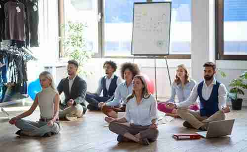 Group,Of,Business,Colleagues,Meditating,At,Work,,Sitting,On,The